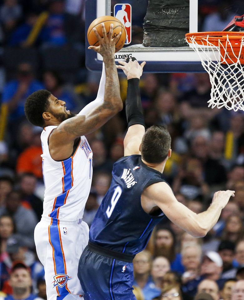 Photo - Oklahoma City's Paul George (13) tries to score against Orlando's Nikola Vucevic (9) during an NBA basketball game between the Oklahoma City Thunder and the Orlando Magic at Chesapeake Energy Arena in Oklahoma City, Monday, Feb. 26, 2018. Oklahoma City won 112-105. Photo by Nate Billings, The Oklahoman