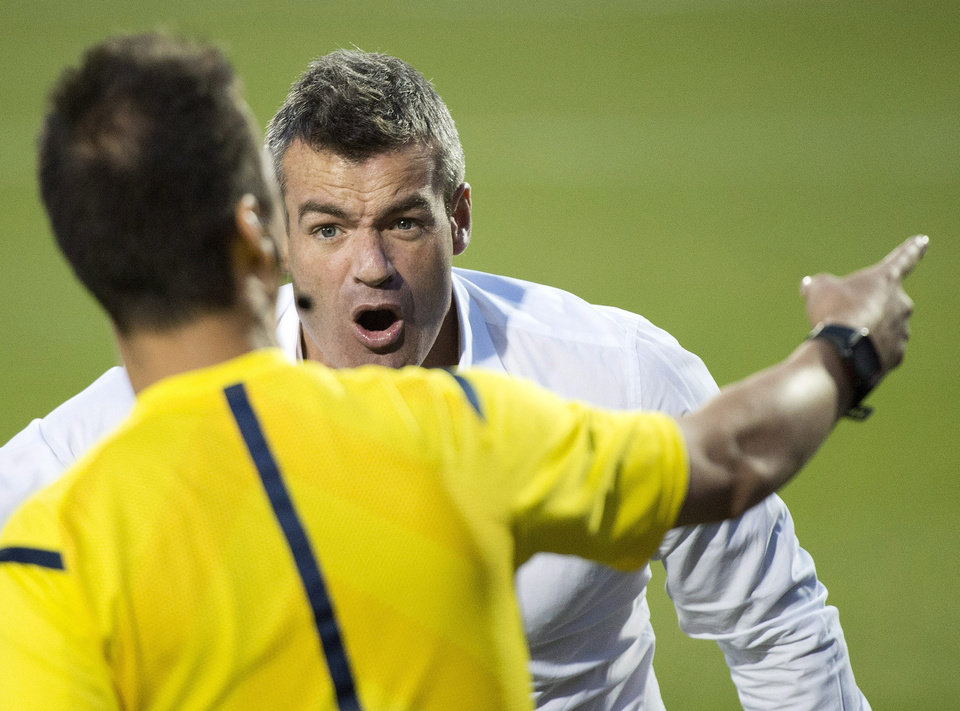 Photo - Toronto FC head coach Ryan Nelsen, right, argues a call with one of the officials while playing against Sporting Kansas City during second-half MLS soccer game action in Toronto, Saturday, July 26, 2014. (AP Photo/The Canadian Press, Nathan Denette)