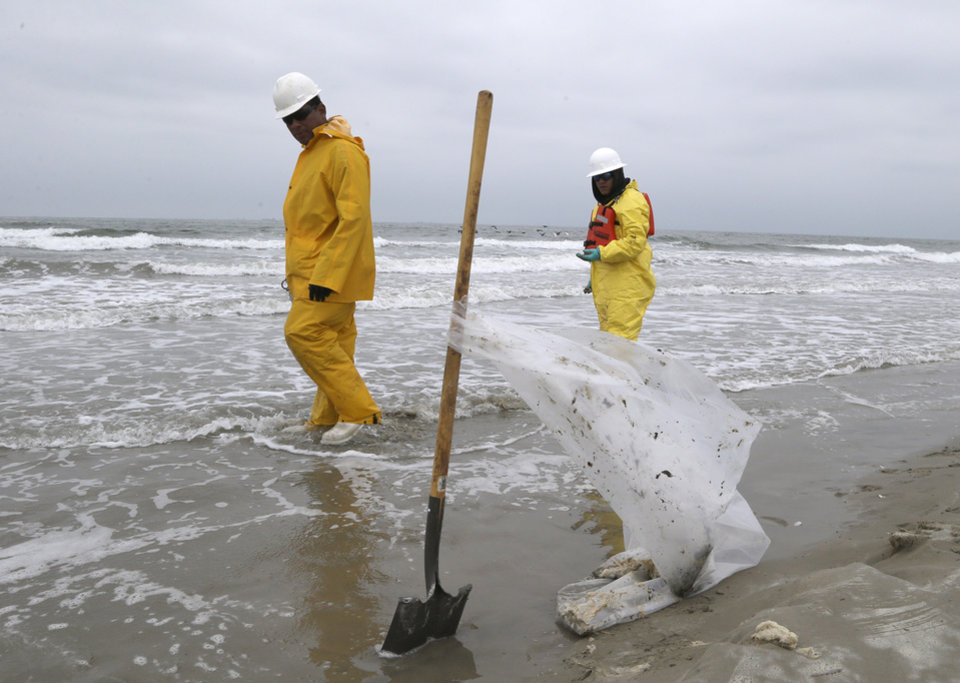Photo -      Workers walk along East Beach near Galveston, Texas, on Monday looking for pieces of oil tar. Thousands of gallons of tar-like oil spilled into the major U.S. shipping channel after a barge ran into a ship Saturday. AP Photo   Pat Sullivan -