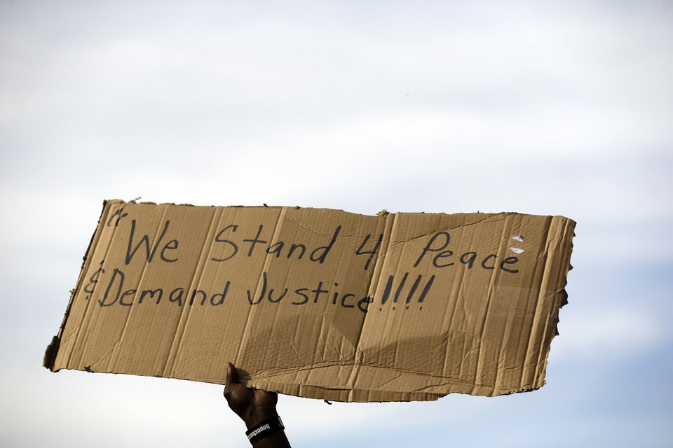 Photo - A demonstrator holds up a sign Thursday, Aug. 14, 2014, at the site where Michael Brown was shot and killed by police in Ferguson, Mo. The Missouri Highway Patrol seized control of a St. Louis suburb Thursday, stripping local police of their law-enforcement authority after four days of clashes between officers in riot gear and furious crowds protesting the death of an unarmed black teen shot by an officer. (AP Photo/Jeff Roberson)