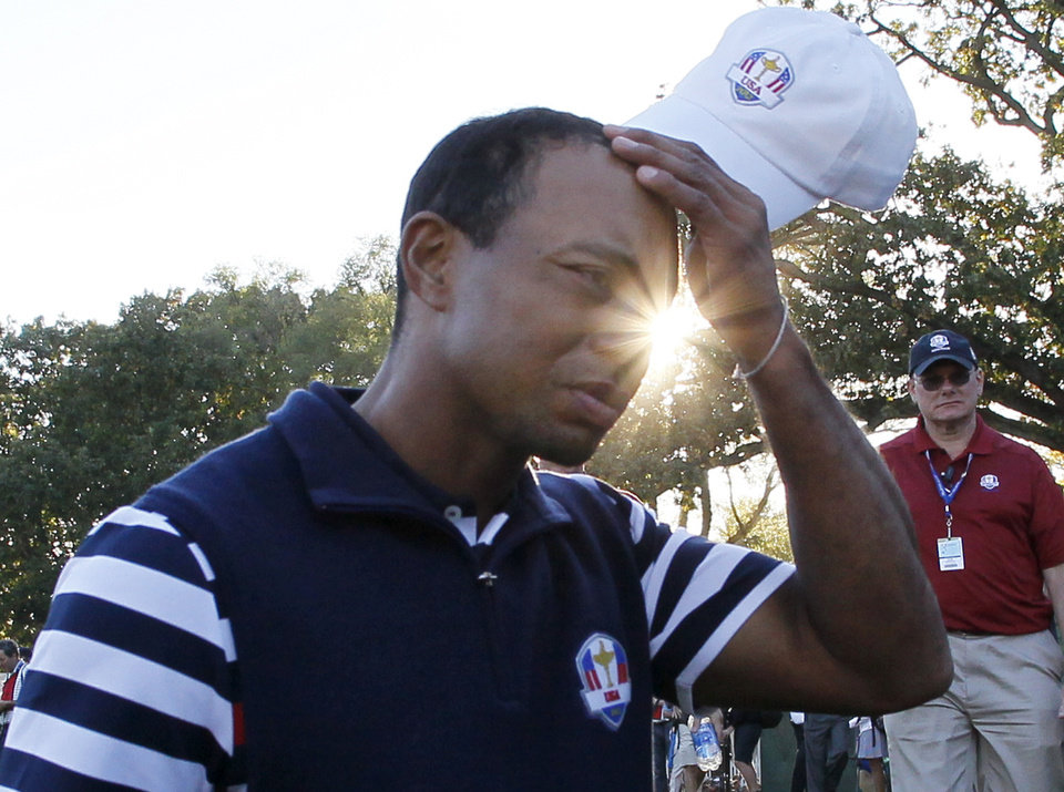 Photo - USA's Tiger Woods scratches his head as he walks off the course after the Ryder Cup PGA golf tournament Sunday, Sept. 30, 2012, at the Medinah Country Club in Medinah, Ill. (AP Photo/Charles Rex Arbogast)  ORG XMIT: PGA209