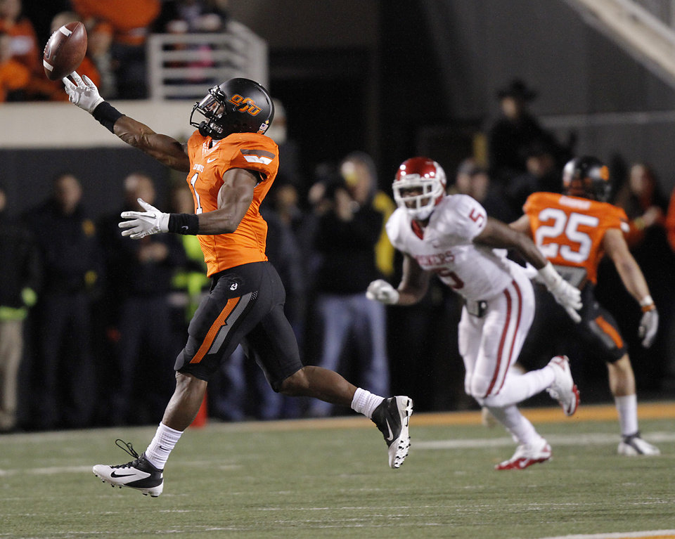 Photo - Oklahoma State's Joseph Randle (1) makes a reception in front of Oklahoma's Joseph Ibiloye (5) during the Bedlam college football game between the Oklahoma State University Cowboys (OSU) and the University of Oklahoma Sooners (OU) at Boone Pickens Stadium in Stillwater, Okla., Saturday, Dec. 3, 2011. Photo by Chris Landsberger, The Oklahoman