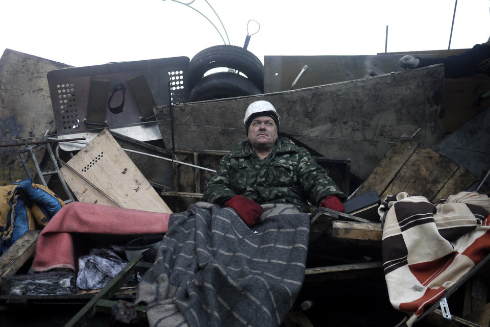 Photo - An anti-government protester sits on a barricade at Independence Square in Kiev, Ukraine, Friday, Feb. 21, 2014. Ukraine's presidency said Friday that it has negotiated an international deal intended to end battles between police and protesters that have killed scores and injured hundreds. (AP Photo/ Marko Drobnjakovic)