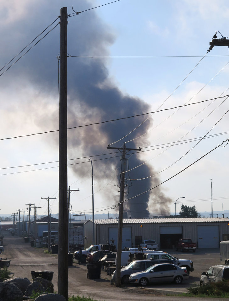 Photo - Smoke rises from the site of a fire in an industrial area of Williston, N.D. on Tuesday, July 22, 2014. Authorities have set up an evacuation zone within a half-mile radius of Red River Supply, the site of the fire. No injuries were immediately reported. Red River Supply provides services to oil companies working in North Dakota's oil patch. (AP Photo/Josh Wood)