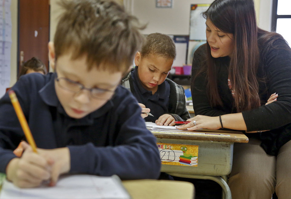 Photo - Second-grade teacher Jennifer Lopez helps students with a writing assignment. Lopez is one of three teachers at at Putnam Heights Elementary School who were trained through the Urban Teacher Preparation Academy. PHOTO BY CHRIS LANDSBERGER, THE OKLAHOMAN  CHRIS LANDSBERGER - CHRIS LANDSBERGER