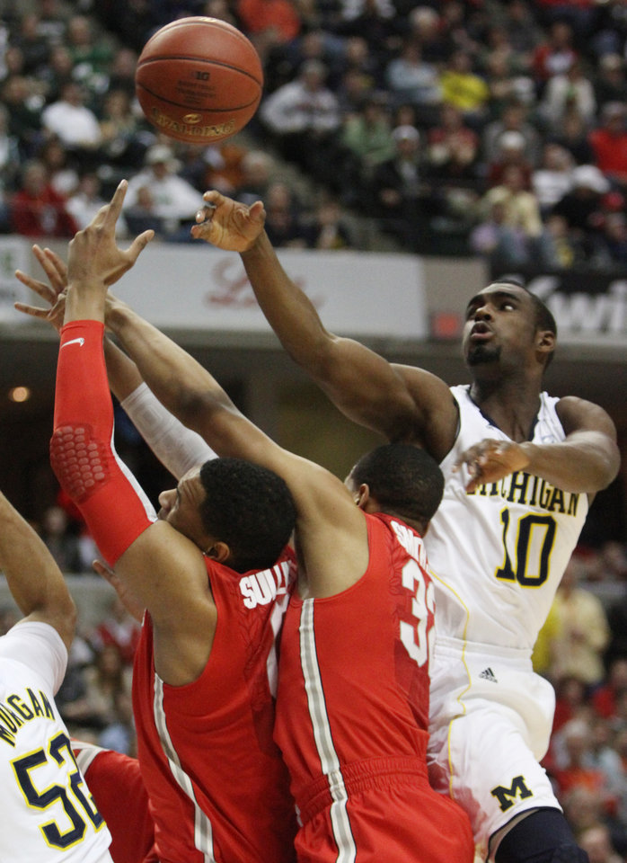 Photo -   Michigan guard Tim Hardaway Jr., right, battles for a rebound against Ohio State guard Lenzelle Smith, Jr. and forward Jared Sullinger, left, in the first half of an NCAA college basketball game in the semifinals of the Big Ten Conference tournament in Indianapolis, Saturday, March 10, 2012. (AP Photo/Kiichiro Sato)