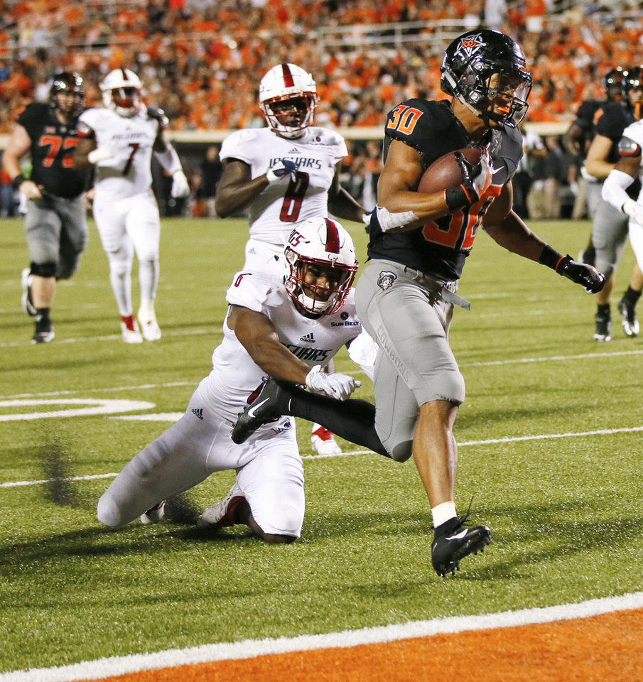 Photo - Oklahoma State's Chuba Hubbard (30) carries the ball in front of South Alabama's Nigel Lawrence (6) for a touchdown in the fourth quarter during a college football game between Oklahoma State (OSU) and South Alabama at Boone Pickens Stadium in Stillwater, Okla., Saturday, Sept. 8, 2018. Photo by Nate Billings, The Oklahoman