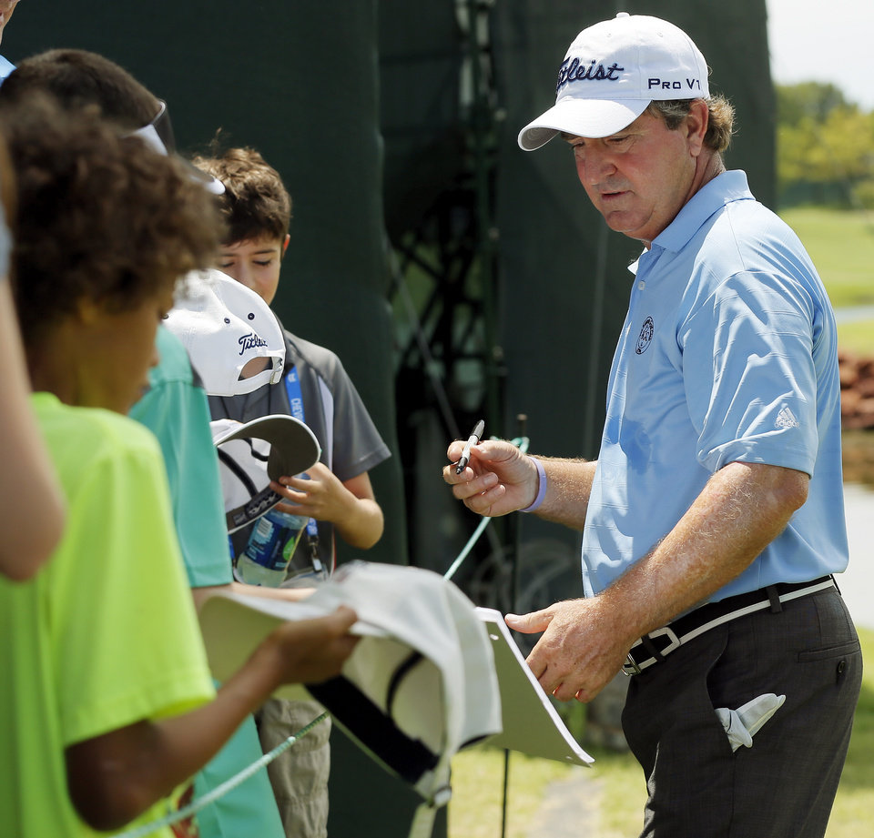 Photo - Gene Sauers signs autographs between holes during practice rounds for the U.S. Senior Open golf tournament at Oak Tree National in Edmond, Okla., Wednesday, July 9, 2014. Photo by Nate Billings, The Oklahoman