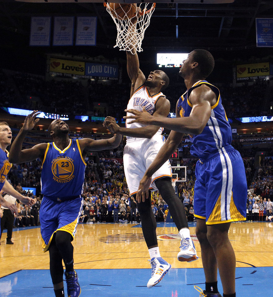 Oklahoma City\'s Serge Ibaka (9) dunks the ball in between Golden State\'s Draymond Green (23) and Harrison Barnes (40) during the NBA game between the Oklahoma City Thunder and the Golden State Warriors at the Chesapeake Energy Arena, Friday, Nov. 29, 2013. Photo by Sarah Phipps, The Oklahoman