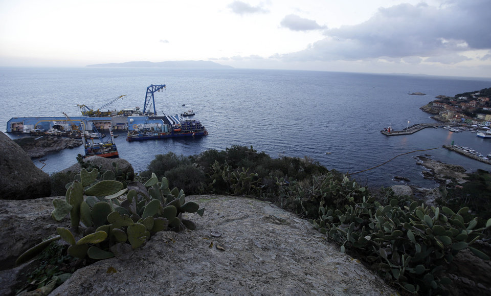 The Costa Concordia cruise ship leans on its side of the Tuscan Island Isola del Giglio, Italy, Saturday, Jan. 12, 2013. More time and money will be needed to remove the Costa Concordia cruise ship from the rocks off Tuscany where it capsized last year, in part to ensure the toxic materials still trapped inside don't leak into the marine sanctuary when it is righted, officials said Saturday. On the eve of the first anniversary of the grounding, environmental and salvage experts gave an update on the unprecedented removal project under way, stressing the massive size of the ship — 112,000 tons, its precarious perch on the rocks off the port of Giglio island and the environmental concerns at play. (AP Photo/Gregorio Borgia)
