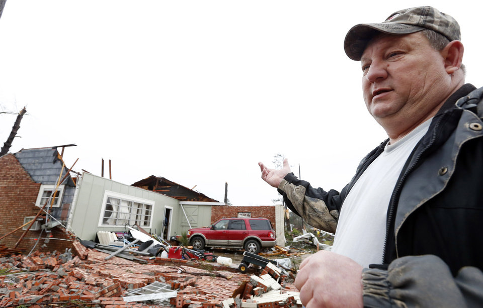 Photo - Randy Wade points to what remains of his house in Petal, Miss., Tuesday, Feb. 12, 2013 following the Sunday afternoon tornado that caused damage throughout this community. Wade, like many other residents was at home with family when the tornado struck, and now works at salvaging what personal items he can while waiting for and insurance adjuster to total his home. (AP Photo/Rogelio V. Solis)