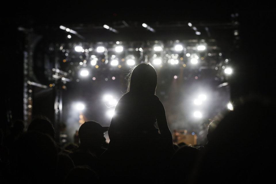 Photo - A child sits on an adult's shoulders while watching Kings of Leon perform during the grand opening of Scissortail Park in Oklahoma City, Friday, Sept. 27, 2019. [Nate Billings/The Oklahoman]
