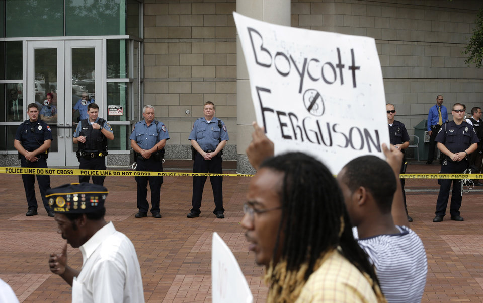 Photo - Protesters march outside the Buzz Westfall Justice Center in Clayton, Mo., Wednesday, Aug. 20, 2014, where a grand jury is expected to convene to consider possible charges against the Ferguson, Mo. police officer who fatally shot 18-year-old Michael Brown. Brown's shooting in the middle of a street has sparked a more than week of protests, riots and looting in the St. Louis suburb. (AP Photo/Charlie Riedel)
