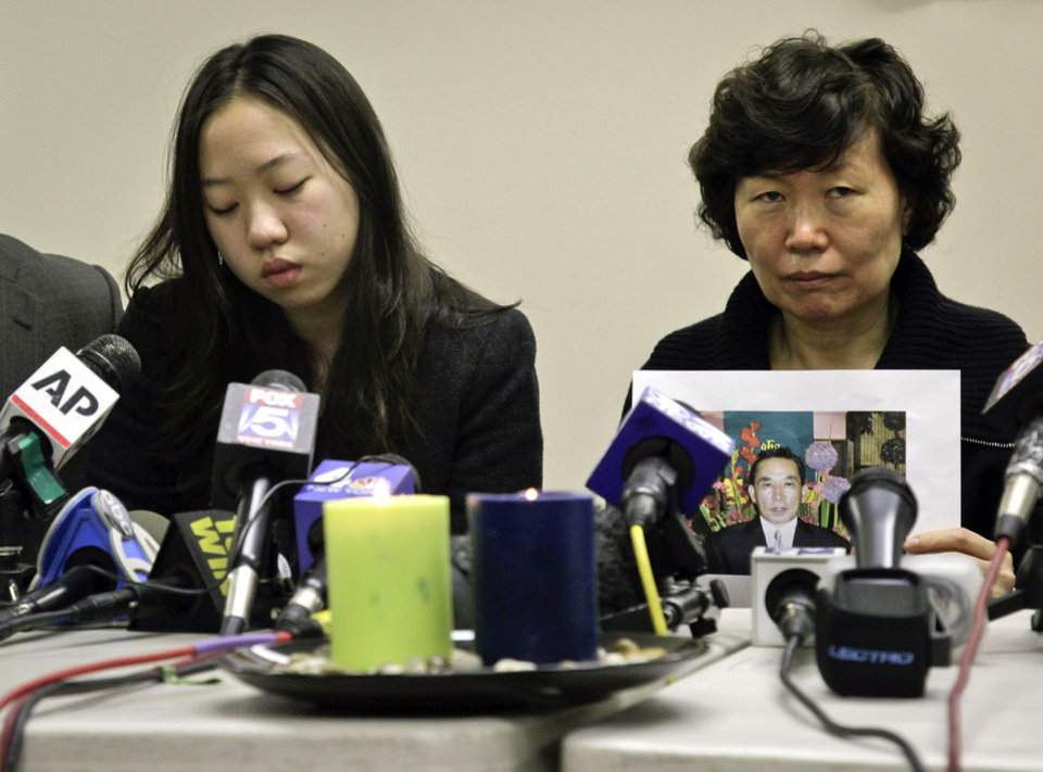 Photo - Serim Han , right, holds a picture of her husband Ki-Suck Han as she sits next to their daughter Ashley Han, 20, during a news conference on Wednesday, Dec. 5, 2012 in New York. A homeless man was arrested Wednesday in the death of Ki-Suck Han, who was pushed onto the tracks and photographed just before a train struck him. (AP Photo/Bebeto Matthews)