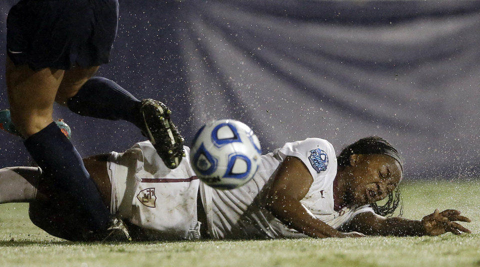 Photo - Florida State's Jamia Fields slips on the wet field during the second half against Penn State in an NCAA women's soccer tournament semifinal, Friday, Nov. 30, 2012, in San Diego. Penn State won, 2-1, in overtime. (AP Photo/Gregory Bull)