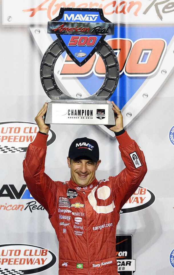 Photo - Tony Kanaan holds the winners trophy after winning the IndyCar Series season final 500 mile auto race Saturday, Aug. 30, 2014, at Auto Club Speedway, in Fontana, Calif. (AP Photo/Will Lester)