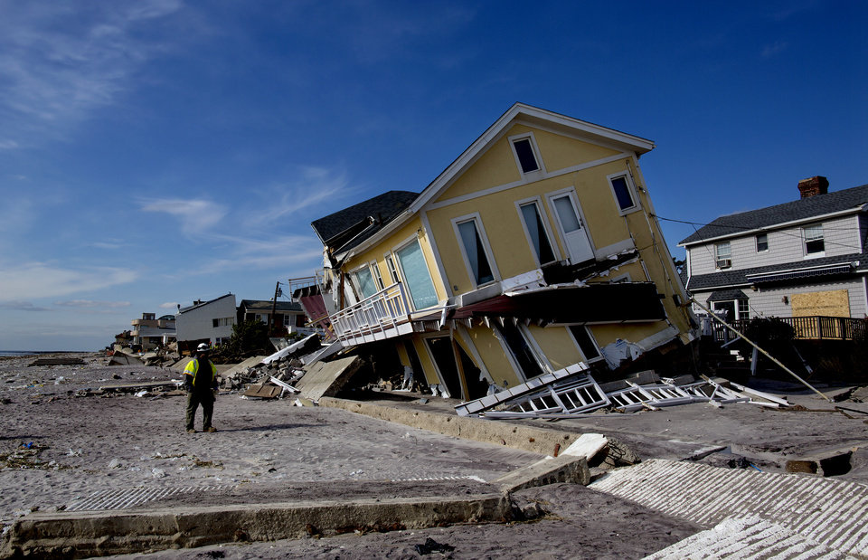 FILE - In this Monday, Nov. 5, 2012 file photo, a damaged home tilts to one side along the beach in the Belle Harbor section of the borough of Queens, New York, in the wake of Superstorm Sandy. A coastal storm that threatens to complicate the Superstorm Sandy cleanup efforts on Wednesday, Nov. 7, 2012 now looks like it will be weaker than expected, experts say. (AP Photo/Craig Ruttle)