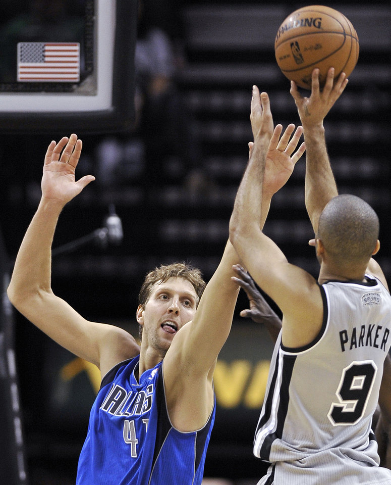 Dallas Mavericks' Dirk Nowitzki, left, of Germany, defends against San Antonio Spurs' Tony Parker, of France, during the second half of an NBA basketball game, Sunday, Dec. 23, 2012, in San Antonio. The Spurs won 129-91. (AP Photo/Darren Abate)
