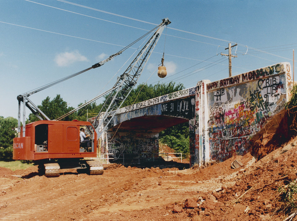 Photo -  Bridge Comes Tumbling Down - The wrecking ball drops on the Graffiti Bridge at NW 59 and Western in Oklahoma City.  The landmark site adorned with writings of all types was torn down Saturday.  Staff photo by Steve Gooch.  Photo dated 06/28/1991 and published on 07/05/1991 in The Daily Oklahoman(C) and again on 07/19/1991 in The Daily Oklahoman(C).