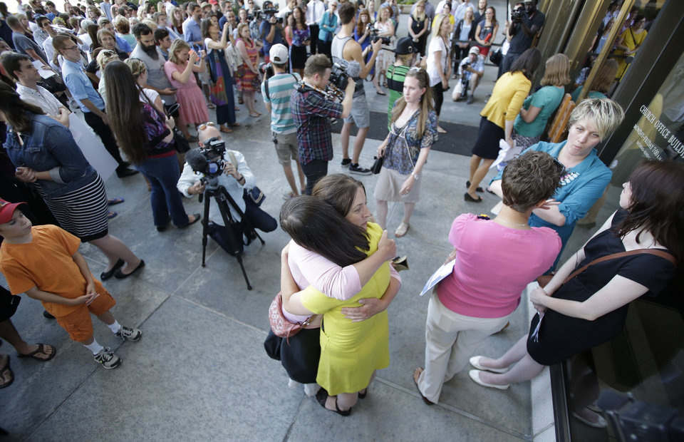 Photo - In this Sunday, June 22, 2014, photo, Kate Kelly, the founder of a prominent Mormon women's group, center right, receives a hug from a supporter during a vigil, in Salt Lake City. Kelly could find out Monday if she will be excommunicated from her church. (AP Photo/Rick Bowmer)