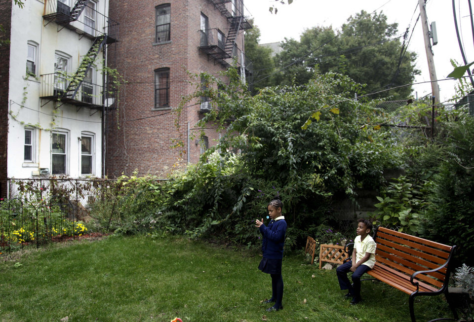Malayasia Blackwood, 7, left, and Samara Johnson, 6, play in the yard of the Drew House in New York, Wednesday, Oct. 3, 2012. The program, called Drew House, is one of a kind in the nation, where mothers arrested on felonies can live with their children, instead of in prison. The program has been lauded as a success that should be replicated around the country, but the small house is already full, and without additional funding and space, it can't grow. (AP Photo/Seth Wenig)