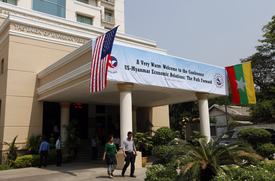 "National flags of Myanmar, right, and the United States decorate the entrance with a banner marking the conference titled ""U.S.-Myanmar Economic Relations: The Path Forward"" at the Union of Myanmar Federation of Chambers of Commerce and Industry (UMFCCI) office Monday, Feb. 25, 2013, in Yangon, Myanmar. Flanked by small national flags, Win Aung, the president of the UMFCCI, Myanmar's main business association, and U.S. Assistant Secretary of State Jose Fernandez shook hands in Yangon Monday and agreed to deepen business ties between their two countries. (AP Photo/Khin Maung Win)"