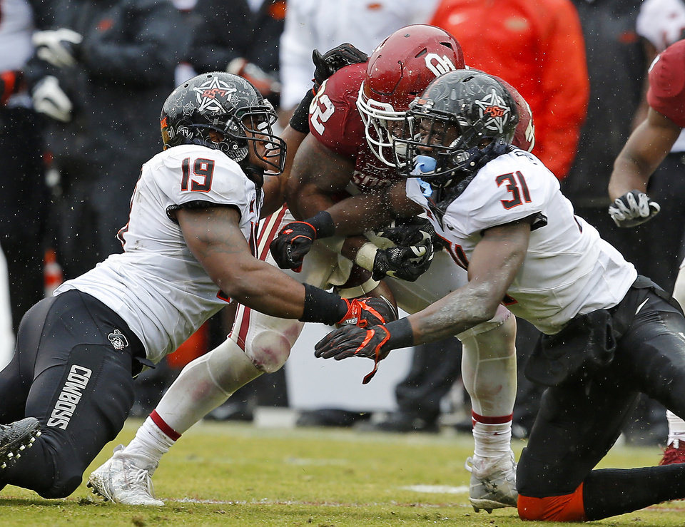 Photo - Oklahoma State's Tre Flowers (31) and Justin Phillips (19) hits Oklahoma's Samaje Perine (32) causing a fumble during the Bedlam college football game between the Oklahoma Sooners (OU) and the Oklahoma State Cowboys (OSU) at Gaylord Family - Oklahoma Memorial Stadium in Norman, Okla., Saturday, Dec. 3, 2016. Oklahoma won 38-20. Photo by Bryan Terry, The Oklahoman