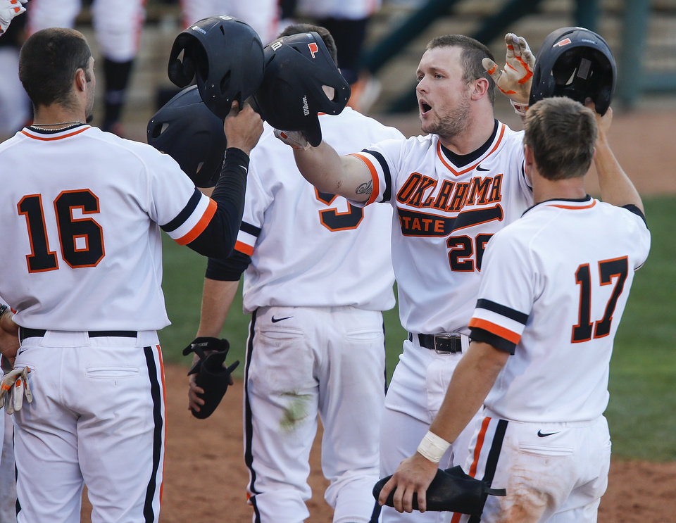 Photo - Oklahoma State's Zach Fish (26) reacts with teammates after hitting a grand slam during the bedlam matchup between the University of Oklahoma and Oklahoma State University in the Phillips 66 Big 12 Baseball Championship in Oklahoma City, Okla. on Wednesday, May 21, 2014.   Photo by Chris Landsberger, The Oklahoman