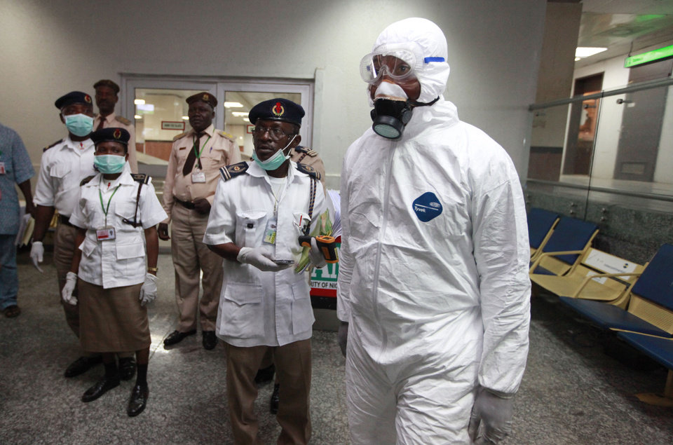 Photo - Nigerian health officials wait to screen passengers at the arrival hall of Murtala Muhammed International Airport in Lagos, Nigeria, Monday, Aug. 4, 2014. Nigerian authorities on Monday confirmed a second case of Ebola in Africa's most populous country, an alarming setback as officials across the region battle to stop the spread of a disease that has killed more than 700 people. (AP Photo/Sunday Alamba)