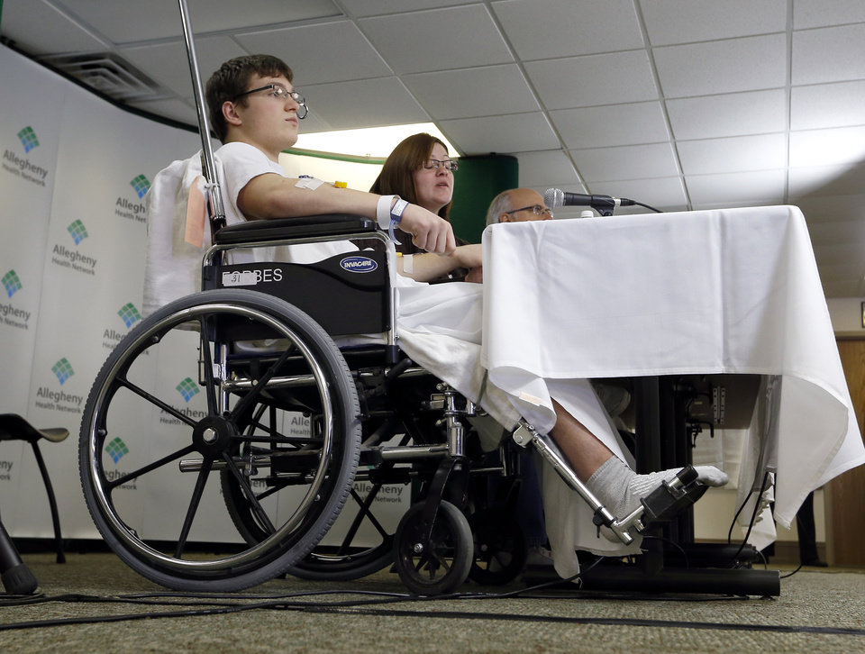 Photo - Brett Hurt, 16, a sophomore at Franklin Regional High School in Murrysville, Pa.,and a victim in the stabbings that took place their on April 9, sits in a wheelchair next to his mother Amanda Leonard during a news conference at Forbes Regional Hospital, Thursday, April 10, 2014, in Monroeville, Pa. Authorities have charged Alex Hribal, 16, with four counts of attempted homicide and 21 counts of aggravated assault in the attack. (AP Photo/Keith Srakocic)
