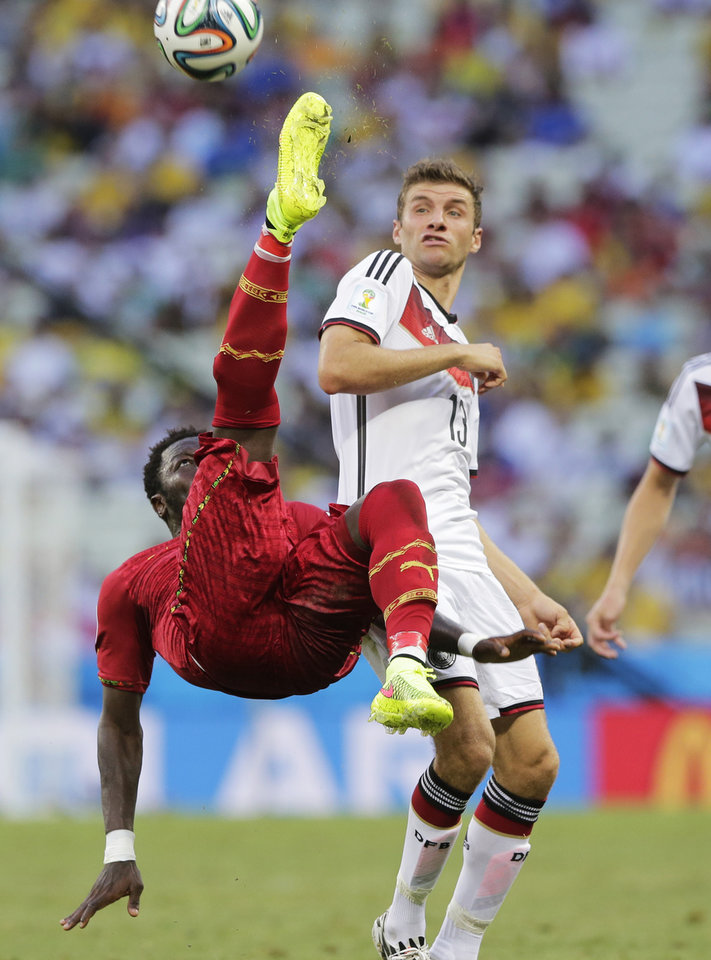 Photo - Ghana's Sulley Muntari clears the ball from Germany's Thomas Mueller during the group G World Cup soccer match at the Arena Castelao in Fortaleza, Brazil, Saturday, June 21, 2014. (AP Photo/Matthias Schrader)