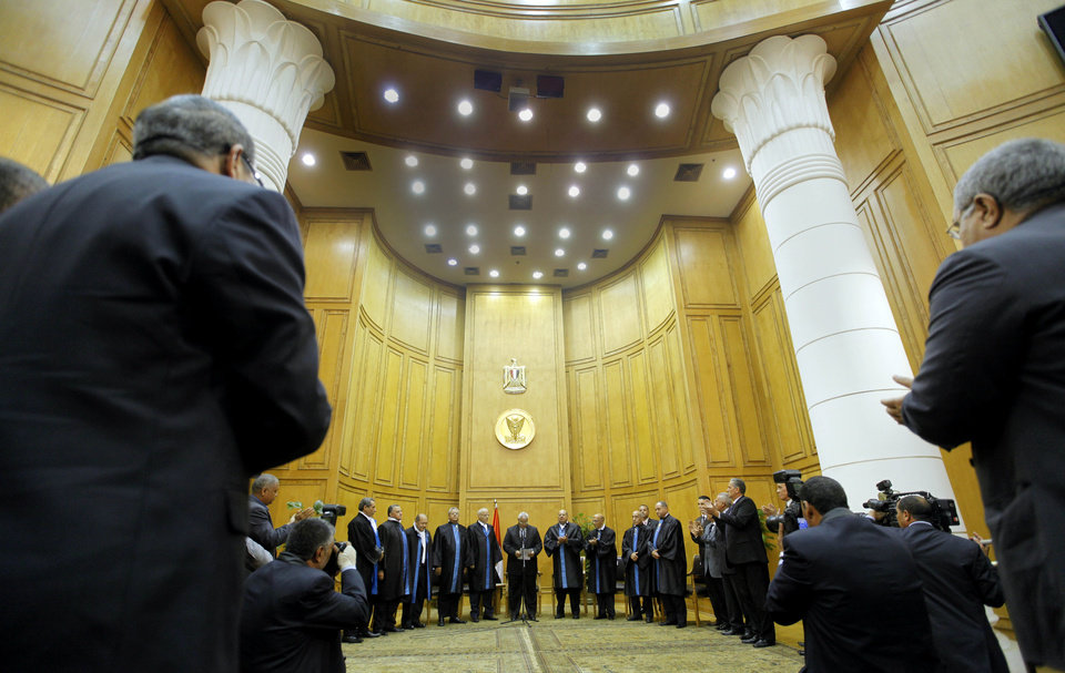 Egypt's chief justice Adly Mansour, center, is applauded at his swearing in ceremony as the nation's interim president Thursday, July 4, 2013. The chief justice of Egypt's Supreme Constitutional Court was sworn in Thursday as the nation's interim president, taking over hours after the military ousted the Islamist President Mohammed Morsi.(AP Photo/Amr Nabil)