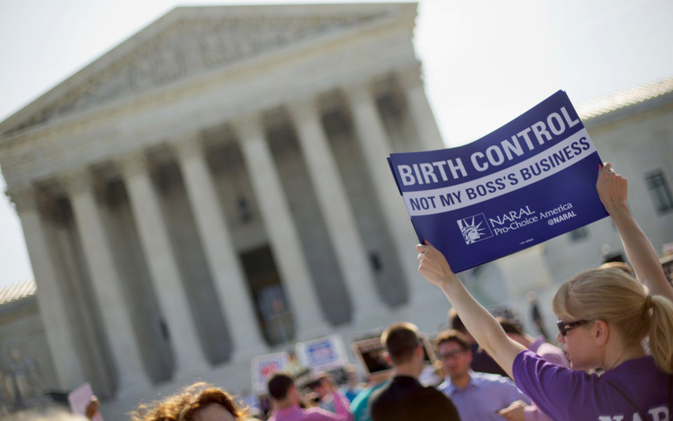 Photo - FILE - This June 30, 2014 file photo shows a demonstrator holding up a sign outside the Supreme Court in Washington on the day the court decided in the Hobby Lobby case to relieve businesses with religious objections of their obligation to pay for women's contraceptives among a range of preventive services the new health law calls for in their health plans. How much distance from an immoral act is enough is the difficult question behind the next legal dispute over religion, birth control and the new health law that is likely to be resolved by the Supreme Court. The issue in more than four dozen lawsuits from faith-affiliated charities, colleges and hospitals who oppose some or all contraception as immoral is how far the Obama administration must go to accommodate them.  (AP Photo/Pablo Martinez Monsivais, File)