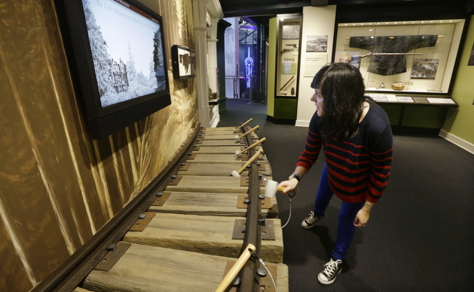 Photo - In this photo taken Wednesday,  Dec. 26, 2012, Karina Chuquihuaccha, a visitors service representative at the museum, tries out an interactive display on railroads at Seattle's Museum of History and Industry, in the city's South Lake Union neighborhood.