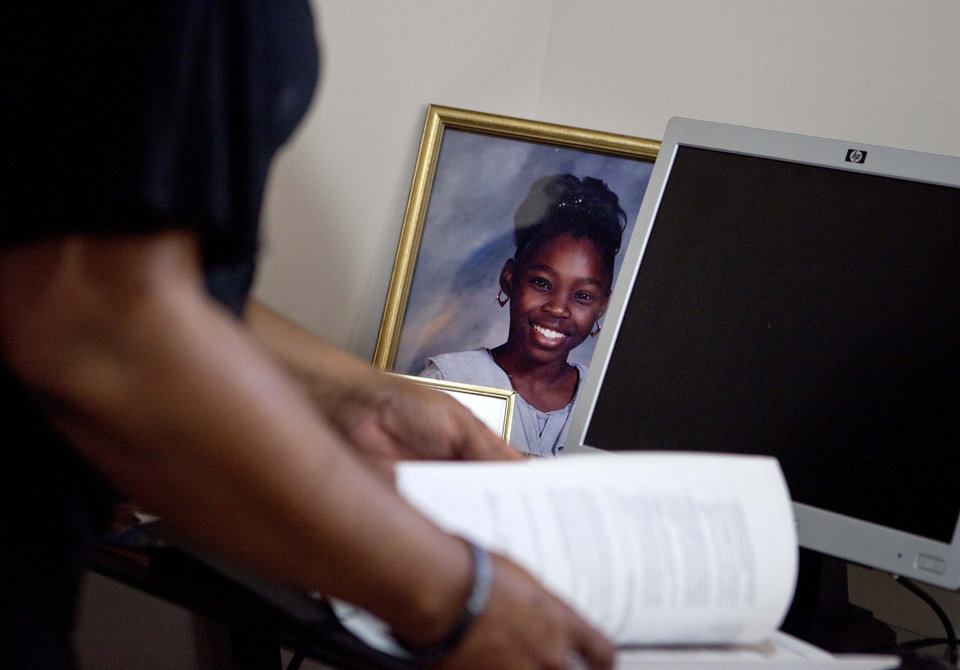 Photo -   Patricia Jackson sifts through bank documents as a picture of her daughter Nakawe sits on the desk in their home Saturday, June 16, 2012, in Marietta, Ga. On a suburban cul-de-sac northwest of Atlanta, the Jacksons are struggling to keep a house worth $100,000 less than they owe. Their voices and those of many others tell the story of a country that, for all the economic turmoil of the past few years, continues to believe things will get better. But until it does, families are trying to hang on to what they've got left. The Great Recession claimed nearly 40 percent of Americans' wealth, the Federal Reserve reported last week. The new figures, showing Americans' net worth has plunged back to what it was in 1992, left economists shuddering. (AP Photo/David Goldman)