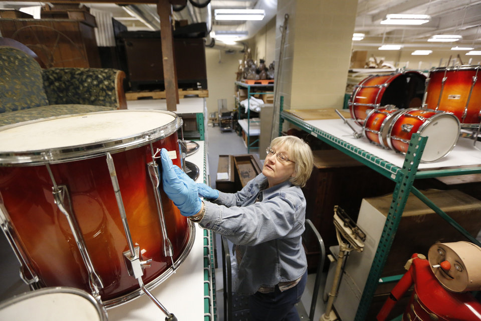 Sherry Massey, senior registrar at the Oklahoma History Center, looks at Jamie Oldaker's drum set. A Tulsa native, Oldaker played with Eric Clapton from 1974-80 and 1983-86. Photo By Steve Gooch, The Oklahoman