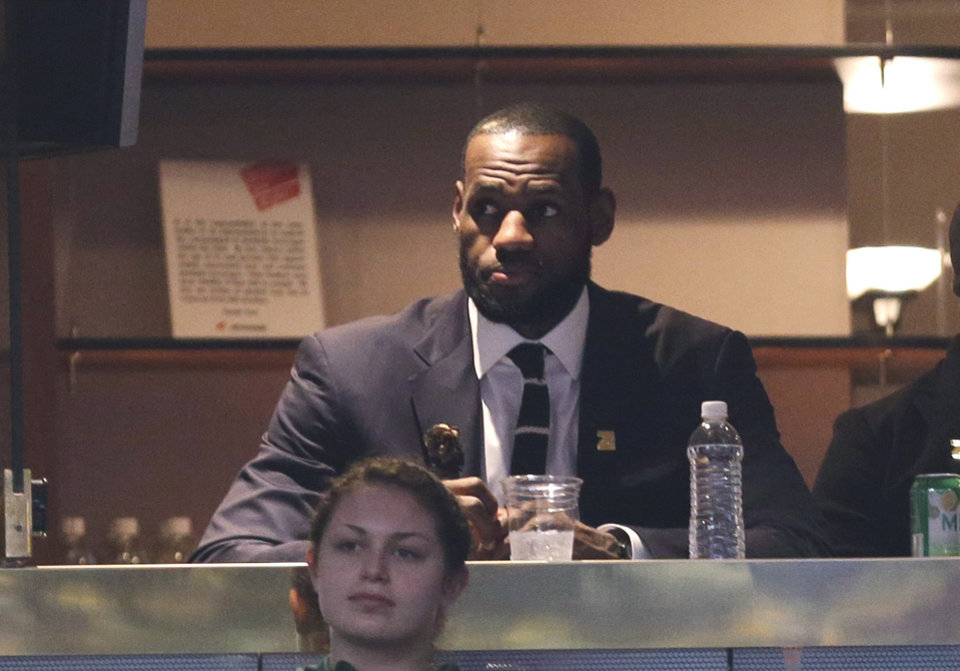 Photo - Miami Heat's LeBron James watches an NBA basketball game between the New York Knicks and the Cleveland Cavaliers on Saturday, March 8, 2014, in Cleveland. (AP Photo/Tony Dejak)