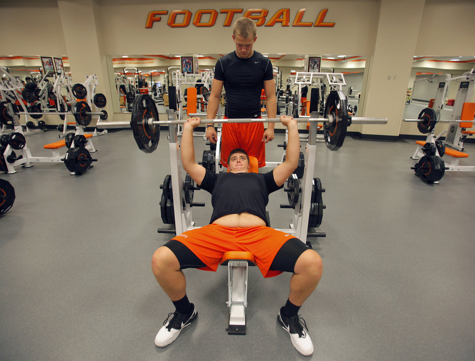 Photo - OKLAHOMA STATE UNIVERSITY / COLLEGE FOOTBALL: Blake Webb, a freshman, spots Grant Canis, a freshman, while he benches during the OSU football team's strength and conditioning training at Boone Pickens  Stadium in Stillwater, Okla., Tuesday, July 17, 2012.  Photo by Garett Fisbeck, The Oklahoman