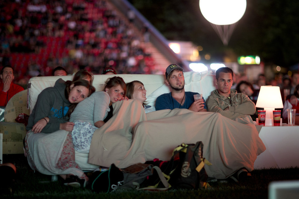 Photo - German soccer fans watch the opening game of the soccer World Cup 2014, while sitting on sofas in the 1.FC Union stadium in Berlin, Thursday, June 12, 2014. (AP Photo/Axel Schmidt)