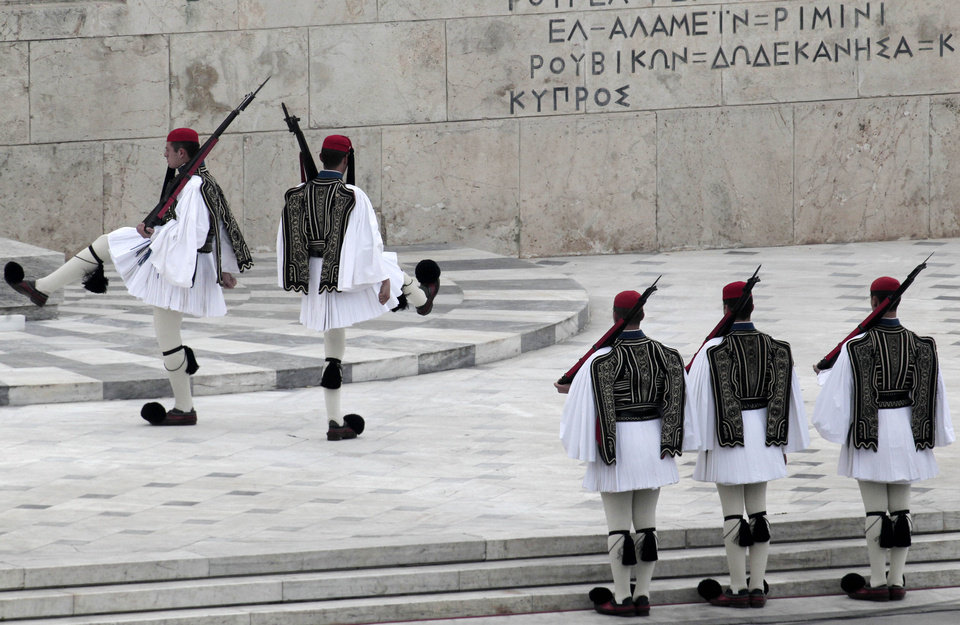 Greek Presidential guards are seen during the changing of the guards at the Unknown Soldier Monument in front of the Parliament in Athens Sunday March 25, 2012. Greek authorities have launched a massive security operation across central Athens for a military parade in the capital to mark the country\'s independence day, for fear that anti-austerity protests could disrupt the march. Thousands of police have been mobilized, while traffic on all major routes leading to the parade area has been blocked off. For the first time, the public will be banned from a large part of the route, including the area in front of Parliament from where politicians and other officials will watch the march. (AP Photo/Dimitri Messinis)