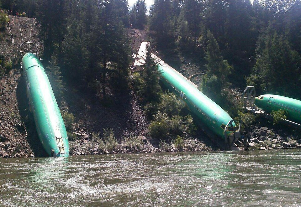 This Sunday, July 6, 2014 photo by Jerry Compton provided by Wiley E. Waters Whitewater Rafting shows a freight train that derailed near Alberton in western Montana, sending three cars carrying aircraft components down a steep embankment and into the Clark Fork River on Thursday, July 3. Removing three Boeing 737 fuselages could take until Tuesday. Montana Rail Link spokeswoman Lynda Frost said a crew of 50 with eight heavy equipment machines is working in conjunction on the steep bank. (AP Photo/Wiley E. Waters Whitewater Rafting, Jerry Compton)