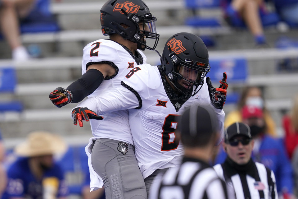 Photo - Oklahoma State wide receivers Tylan Wallace (2) and Braydon Johnson (8) celebrate a touchdown during the first half of an NCAA college football game against Kansas in Lawrence, Kan., Saturday, Oct. 3, 2020. (AP Photo/Orlin Wagner)