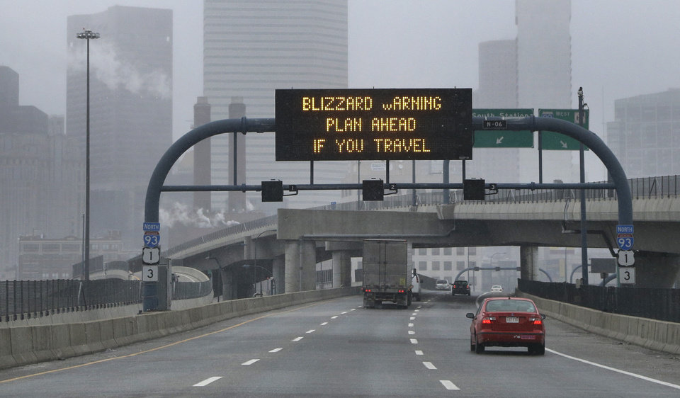 Photo - A warning sign flashes for motorists on the expressway into Boston as snow starts to fall on Friday, Feb. 8, 2013. A major winter storm is heading toward the U.S. Northeast with up to 2 feet of snow expected for a Boston-area region that has seen mostly bare ground this winter. (AP Photo/Elise Amendola)