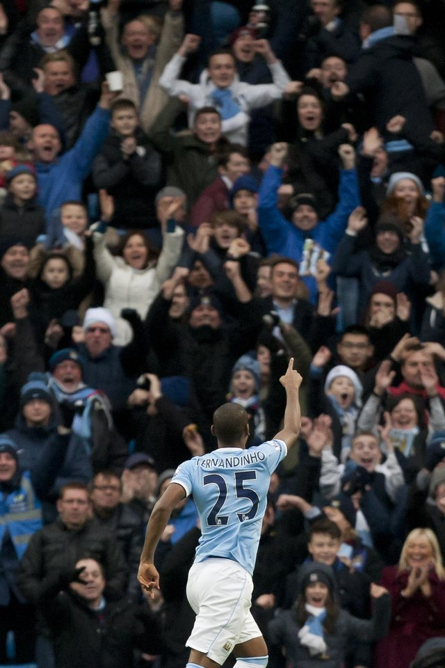 Photo - Manchester City's Fernandinho celebrates after scoring against Arsenal during their English Premier League soccer match at the Etihad Stadium, Manchester, England, Saturday Dec. 14, 2013. (AP Photo/Jon Super)