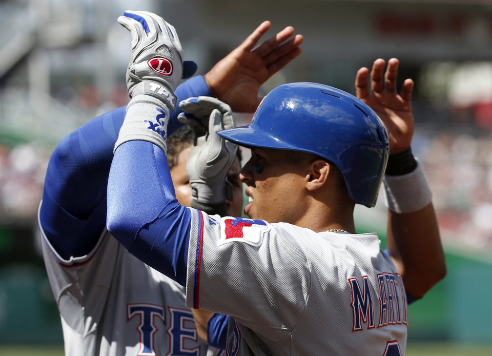 Photo - Texas Rangers' Leonys Martin, right, celebrates his solo home run Elvis Andrus during the seventh inning of a baseball game against the Washington Nationals at Nationals Park, Sunday, June 1, 2014, in Washington. (AP Photo/Alex Brandon)