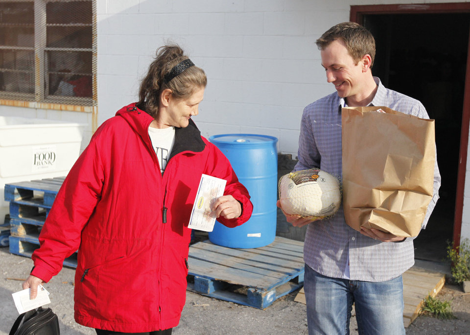 Volunteer Daniel Holdge helps Deborah Wood during the annual Easter food basket distribution at the Jesus House. Photos By Paul Hellstern, The Oklahoman