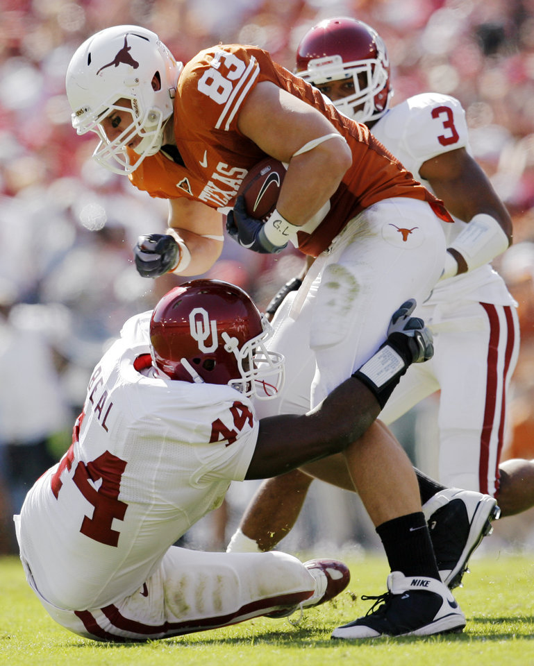 Photo - OU's Jeremy Beal (44) tackles Greg Smith (83) of Texas in front of OU's Jonathan Nelson (3) during the Red River Rivalry college football game between the University of Oklahoma Sooners (OU) and the University of Texas Longhorns (UT) at the Cotton Bowl in Dallas, Texas, Saturday, Oct. 17, 2009. Photo by Nate Billings, The Oklahoman