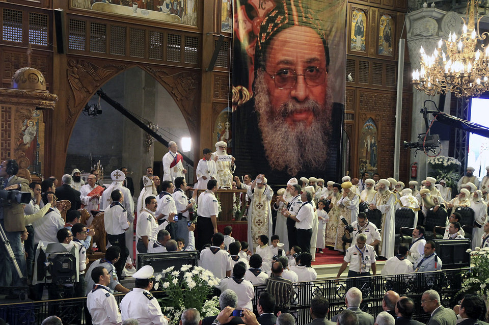 The congregation watches Acting Coptic Pope Pachomios, center, displays the name of 60-year-old Bishop Tawadros, soon to be Pope Tawadros II, during the papal election ceremony at the Coptic Cathedral in Cairo, Egypt, Sunday, Nov. 4, 2012. Egypt's ancient Coptic Christian church named a new pope on Sunday, chosen in an elaborate ceremony where a blindfolded boy drew the name of the next patriarch from a crystal chalice. Bishop Tawadros will be ordained Nov. 18 as the spiritual leader of a community that increasingly fears for its future amid the rise of Islamists to power in the aftermath of last year's uprising. (AP Photo/Sami Wahib)