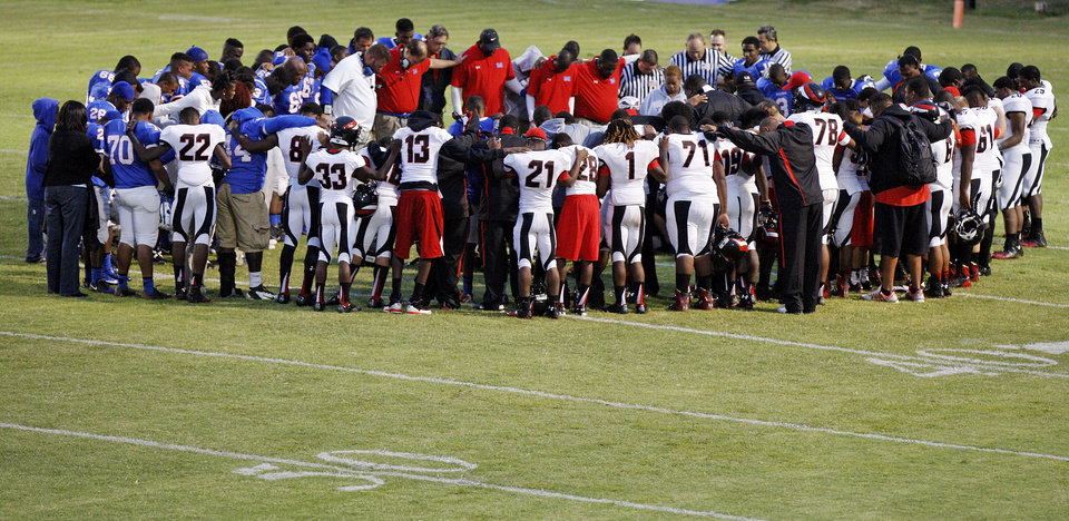 Photo - Players, coaches and officials bow their heads as emergency medical workers check on Millwood's Andre Clanton (22) during a high school football game between Millwood and Prime Prep Academy in Oklahoma City, Friday, Sept. 14, 2012. Clanton was taken from the game in an ambulance. Photo by Nate Billings, The Oklahoman