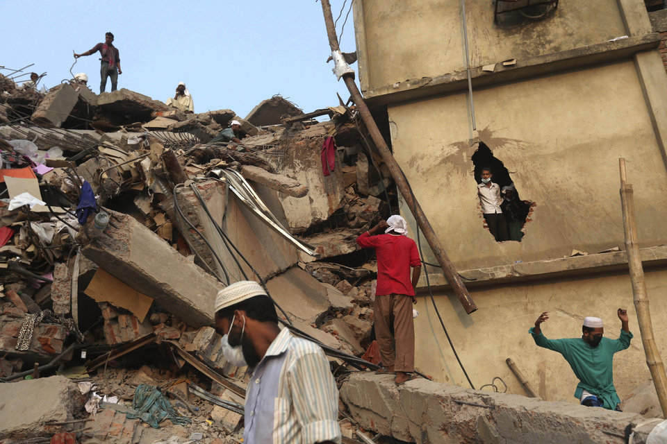 Photo - Bangladeshi rescue workers search the rubble at the site of a building that collapsed Wednesday in Savar, near Dhaka, Bangladesh, Friday, April 26, 2013. The death toll reached hundreds of people as rescuers continued to search for injured and missing, after a huge section of an eight-story building that housed several garment factories splintered into a pile of concrete.(AP Photo/Kevin Frayer)